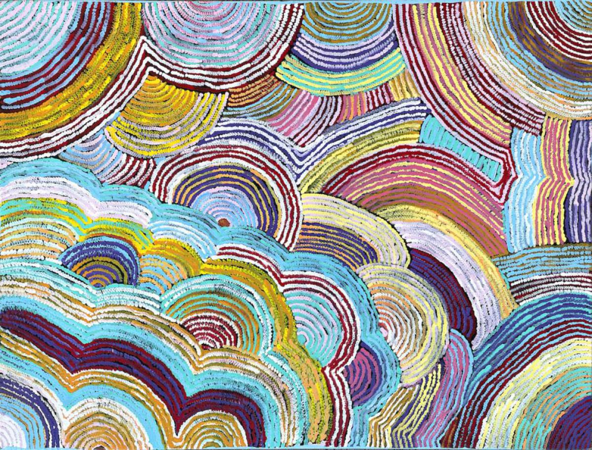 """Eunice Napanangka Jack's paintings are interpretations of her country near Lake Mackay. She uses layers of colour to build up a vision of the bush flowers and grasses. Amongst this landscape Eunice's personal stories are told, either of the travellings of her """"Tjukurrpa"""" - the Bilby - or the people who once lived in the area."""