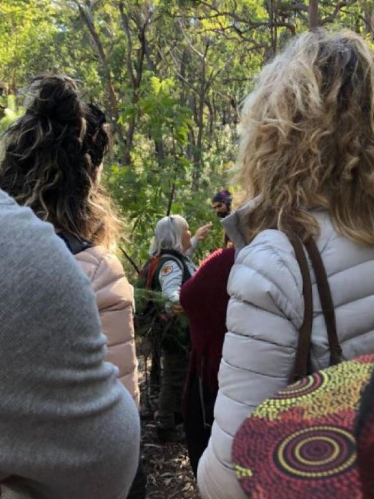 Aboriginal Discovery Ranger with participants looking on.