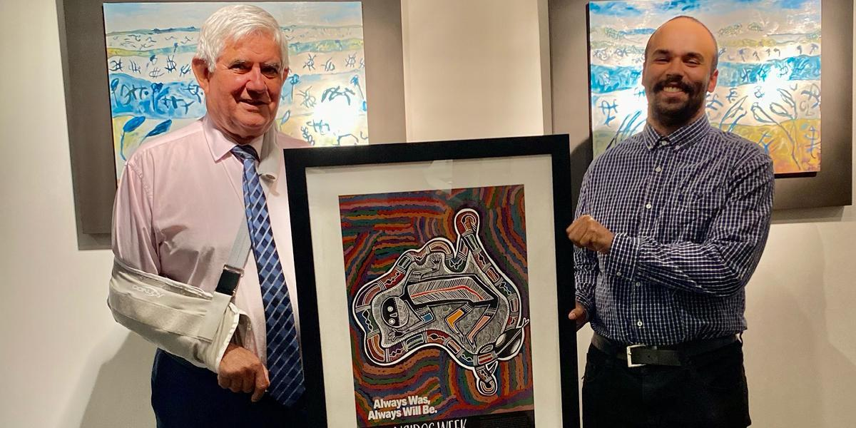 The Hon Ken Wyatt AM MP holding the 2020 NAIDOC Poster with the artist, Tyrown Waigana