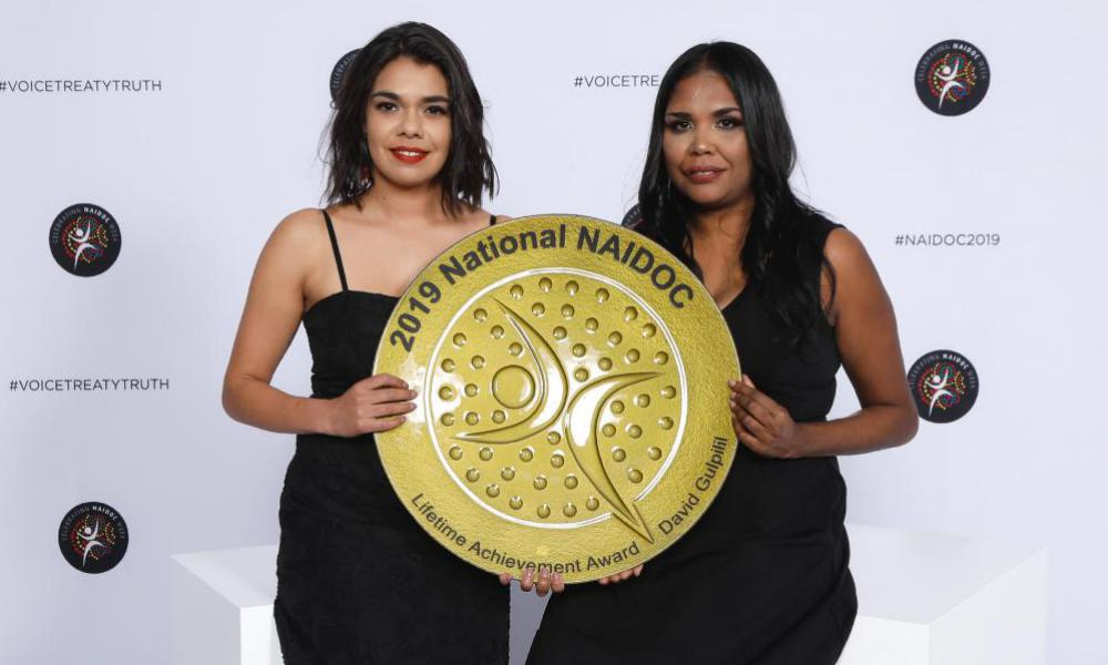 Two women hole a trophy '2019 National NAIDOC