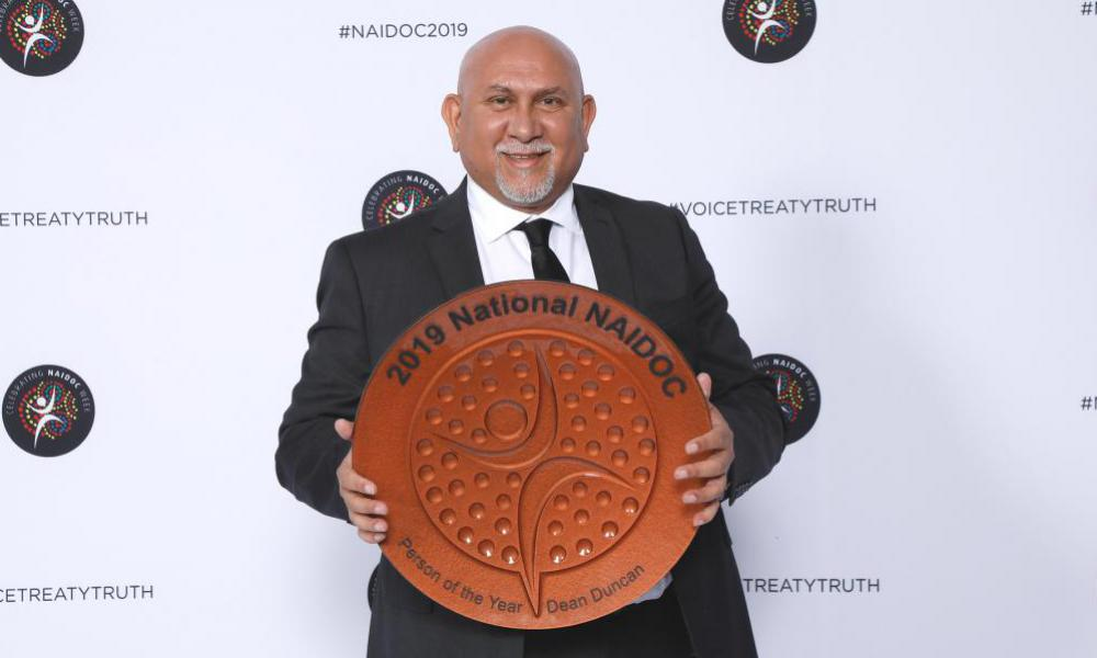 Man stands holding an Award: 2019 National NAIDOC